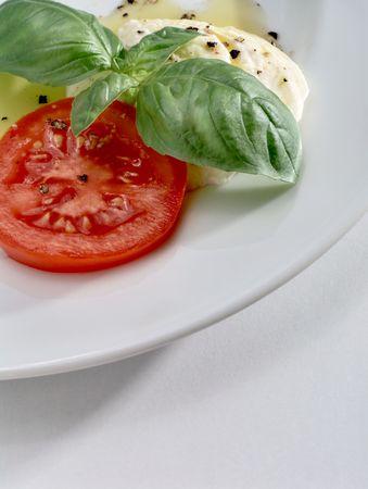 Mozzarella, Blätter frische Tomaten Slice und aromatisch basilikum mit Olivenöl und schwarzem Pfeffer auf weißen Teller  Standard-Bild - 5453367