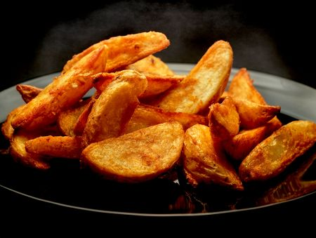 Hot spicy potato wedges on black plate