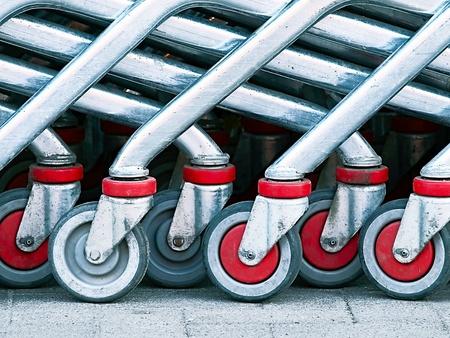 Gruppe des roten und grauen Einkaufswagens dreht sich auf einen Bürgersteig Standard-Bild - 9747833