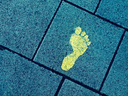 footmark: Yellow paint footprint on bluish sidewalk