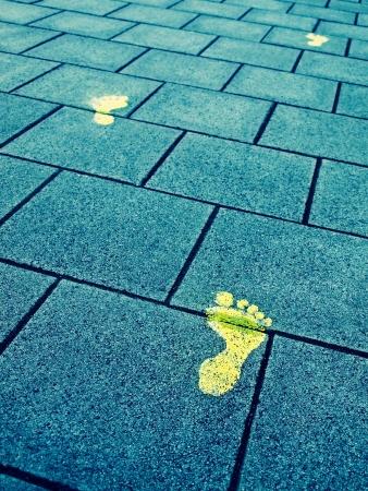 lonesome: Yellow paint footprints on sidewalk symbolize progress Stock Photo