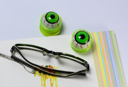 funny glasses: An eye glasses and funny eyeball on working table.