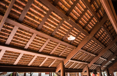 thai style: the wooden structure under the clay roof use so many small pieces of long wood to support all the clay roof tile Stock Photo