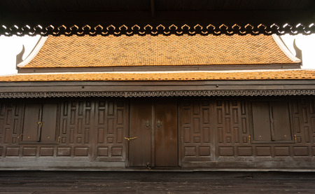 A large wooden Thai house in dark brown color with a typical clay roof and good designed Stok Fotoğraf