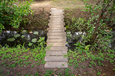 The wooden bridge in a small garden made from wood to cross the small ditch.