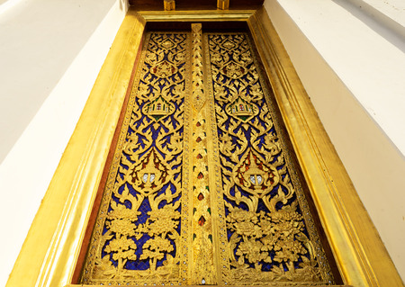 huge golden door made from teakwood and painted with gold color in Thai style Stok Fotoğraf