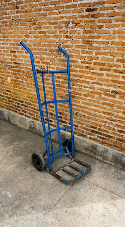 a blue iron pushcart stay nearby the brick wall.
