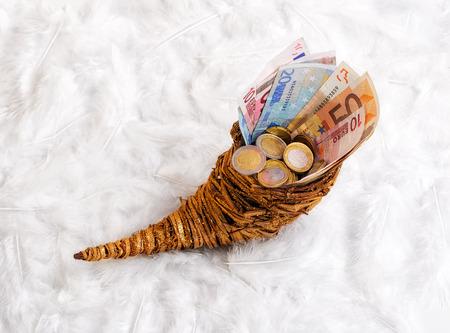 cornucopia - bills and change in a horn of plenty