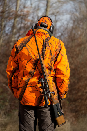 safety vest: hunter with gun wearing safety vest Stock Photo