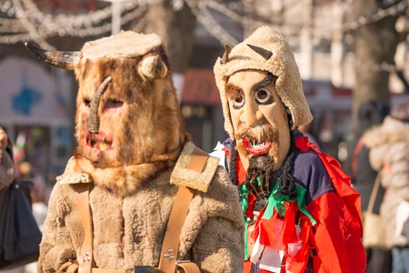Two dancers called kukers march and one of them looks in camera at ritual at the annual International Festival of Masquerade Games Surva in Pernik, Bulgaria