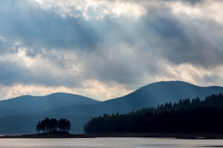 Silhouette of small natural island with pine trees and layered mountain hills background. Moody colorful image with overwhelming blue color at Shiroka Polyana lake, Bulgaria, Rhodope mountain Stock Photo
