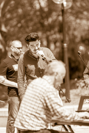 DIMITROVGRAD, BULGARIA - APRIL 30, 2018: Male jazz singer performs on microphone between pianist and saxophonist at street concert event dedicated to International World Jazz Day Editorial