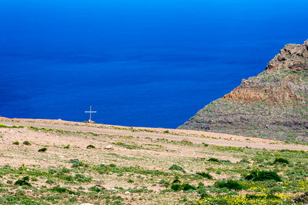 Lanzarote, Canary Islands, Spain, elevated landscape view of the blue Atlantic Ocean with Christian cross on a tomb near a dirt road close to the shore 免版税图像