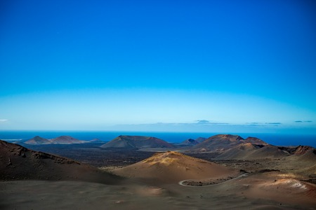 If it wasnt the Ocean, this would look like Moon scape. The vast emptiness and loneliness of the Lanzarote black frozen lava volcanic desert with few sleeping volcanoes and almost clear blue sky 版權商用圖片