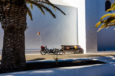 FEMES, SPAIN - FEBRUARY 14, 2015: Exhausted male tricycle rider sleeps on public bench near the walls of the San Marcial del Rubicon church under the afternoon sun in Lanzarote, Canary Islands Editorial