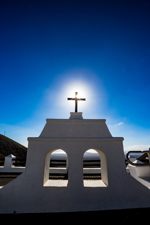 Hot Sun coming through the famous black Christian cross at the beautiful spot called Mirador De Femes in Lanzarote, Canary Islands, Spain. Two white windows and clear blue spring sky background