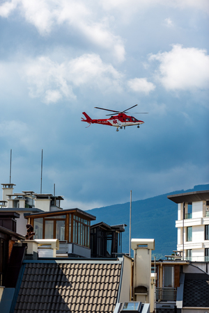 SOFIA, BULGARIA - JUNE 08, 2016: Medical rescue red cross helicopter flies over Sofia, the capital of Bulgaria during training mission. Cloudy springtime day Editorial