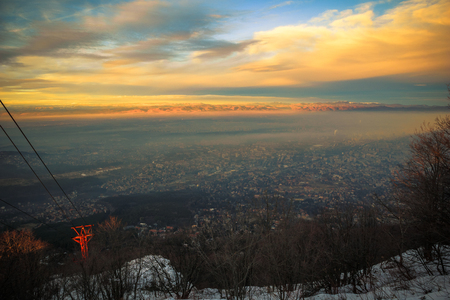 Sofia city foggy mountain golden hour view, moments before the sunset from the Kopitoto Hill, Vitosha Mountain, Sofia, Bulgaria with parts of the old abandoned cable car from Knyazhevo village 写真素材