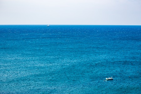 Two boats in the blue waters of Adriatic Sea in a clear but windy spring day, focus on the back boat. Calm scene, crystal background