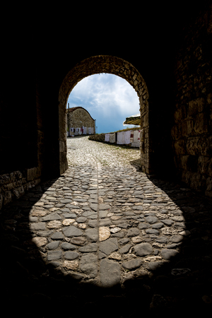 Curvy shape of the entrance of the Berat Castle in Albania, sunny springtime day with stone street, shadows and cloudy spring sky