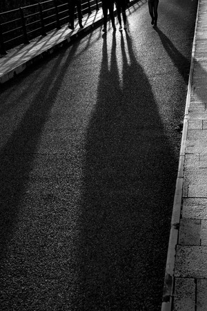 Long evening shadows of four young persons, friends, walking towards the camera, black and white image, partial legs, feet, Sun light reflection on the road, sidewalk. Back-lit silhouettes in Greece