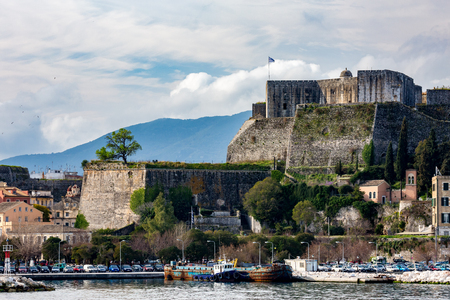 CORFU, GREECE - MARCH 5, 2017: Several cars are parked at ferryboat port of Corfu, Kerkira island in beautiful puffy clouds sky in calm spring day with ancient fort with Greek flag in background Redakční