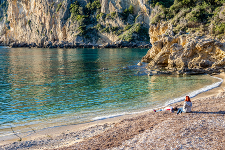 Two unrecognizable women rest on pebbly beach, Corfu, Greece, crystal clear sea water in sunny spring day Standard-Bild