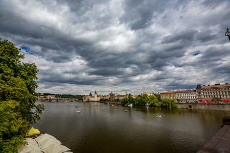 Water transport as leisure near bridge on Vltava River in Prague, Czech Republic. Dramatic clouds summer sky in the capital, green poplar trees surround the riverbed in this travel destination 免版税图像