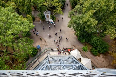 PRAGUE, CZECH REPUBLIC - AUGUST 28, 2015: Several tourists wait to enter Petrin observation and lookup tower in Petrin park in West Prague, Czech Republic. Warm summer day, view from high above Sajtókép
