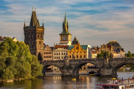 PRAGUE, CZECH REPUBLIC - AUGUST 27, 2015: Tour boats sail and pass under the medieval stone Charles Bridge on Vltava River, Prague, Czech Republic in calm summer evening with people walking on top