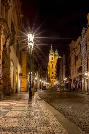 PRAGUE, CZECH REPUBLIC - AUGUST 28, 2015: Long exposure blurs people movement on street in Lesser Town, West bank Vltava river, Prague, capital of Czech Republic in summer. Light diffraction effects