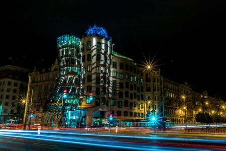 PRAGUE, CZECH REPUBLIC - AUGUST 28, 2015: Famous Dancing House is illuminated with bright lights during nights, Prague, capital of Czech Republic in summer. Motion blur lines from the road traffic