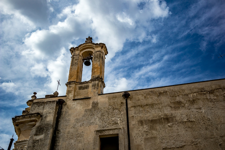 The amazing medieval Church of Madonna dei Martiri in the stunning town of Altamura in the Puglia region, South Italy. Close-up street detail view. Lovely sunny summer day with puffy white clouds 免版税图像