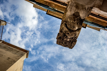 Square head architectural detail from the historic center of Altamura, Italy, Puglia region, alternative view from below, scenery summer day with puffy white clouds