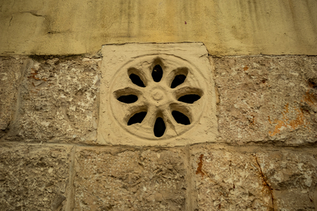 External eight leaves rose-window, yellow limestone fenestra, on residential building in the historic center of Altamura, Italy, Puglia region