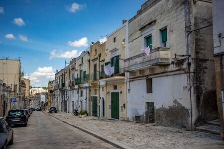 MATERA, ITALY - AUGUST 27, 2018: Warm scenery summer day view from empty street just before entering the old part of the amazing ancient town. This residential part is just on top of the famous sassi