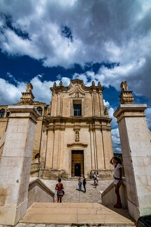 MATERA, ITALY - AUGUST 27, 2018: Warm scenery summer day street view in front of Chiesa di SantAgostino in the ancient town of the Sassi. Tourists enter the yard of the beautiful medieval church