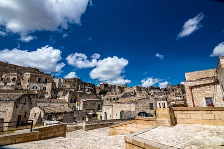 Summer day scenery street view of the amazing ancient town of the Sassi with white puffy clouds moving on the Italian blue sky. Matera, Basilicata, Italy