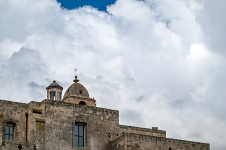 Summer blue sky and church roof with religious cross, view of ancient town of Matera, the Sassi di Matera, Basilicata, Southern Italy, cloudy summer August day Stock Photo