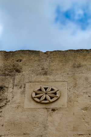 External eight leaves rose-window, yellow limestone fenestra, on residential building in the historic center of Matera, Italy, Basilicata region