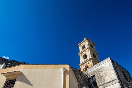 The beautiful church bell tower with Christian cross in Laterza, Italy, Clear August summer cloudless blue sky