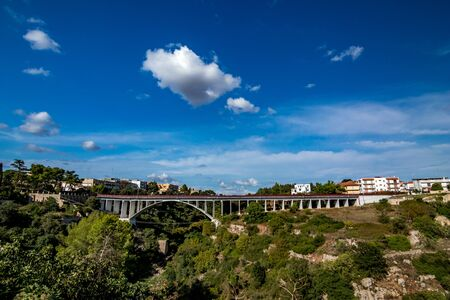 Picturesque view of the bridge across the gorge at Laterza, or Gravina di Laterza, Puglia region, Southern Italy in summertime, beautiful blue sky with few clouds