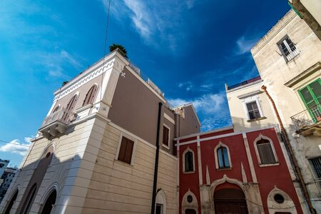 Beautiful facade of building in Puglia. Mediterranean architecture of Southern Italy. Scenery summer blue-sky day with expressive clouds. Day street alleyway view, European travel photography 스톡 콘텐츠