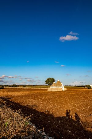 Landscape with typical amazing architecture of truli in the brown soil land in Puglia region, near the town of Alberobello, Southern Italy. Late afternoon lighted by golden Sun rays, warm summer day 스톡 콘텐츠