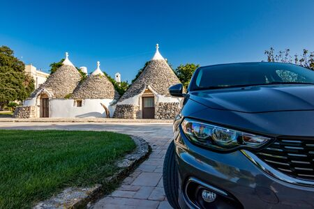 Morning photo of typical Italian Truli near Alberobello in Puglia region. Trulli are declared Unesco heritage. Defocused front part of modern car in the foreground. Clear summer August blue sky