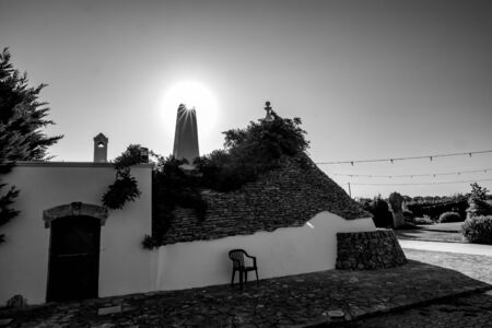 Cityscape with typical amazing architecture of truli with chimney light diffraction against the Sun in Puglia region, near the town of Alberobello, Southern Italy. Warm summer morning, black and white