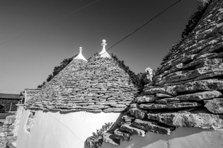 Cityscape with typical amazing architecture of truli with beautiful roofs lighted by the Sun in Puglia region, near the town of Alberobello, Southern Italy. Warm summer morning, black and white 스톡 콘텐츠