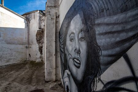 LATERZA, ITALY - AUGUST 27, 2018 - Black and white street art graffiti of woman smiles from the white walls in pedestrian pass way in the province of Puglia in Southern Italy, sunny summer day Редакционное