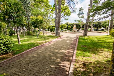 Alley in the tree shadows with round square and fountain in public park, Noci. Puglia. Italy, sunny and warm summer day