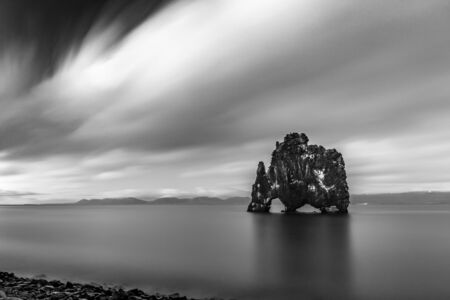 Black and white long exposure photograph, 377 s, of the famous sea rock of Hvitserkur, Northern Iceland. Taken in the summer in the blue hour. Nice clouds motion blur, soft contrast, imaginary figure 写真素材